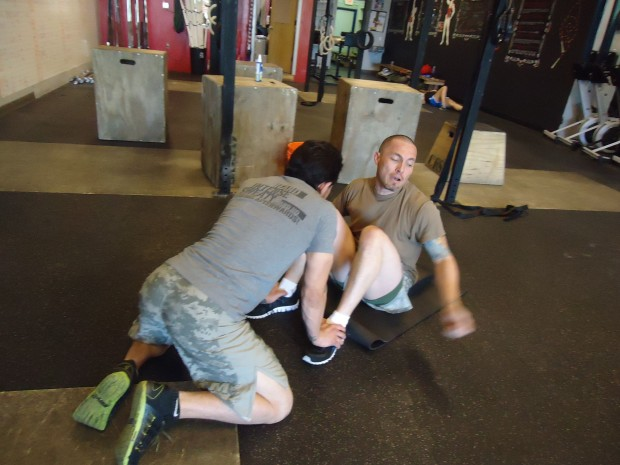 Everyone needs a buddy. Dario Jimenez and John Salazar help each other do as many sit ups as possible in 2 minutes.